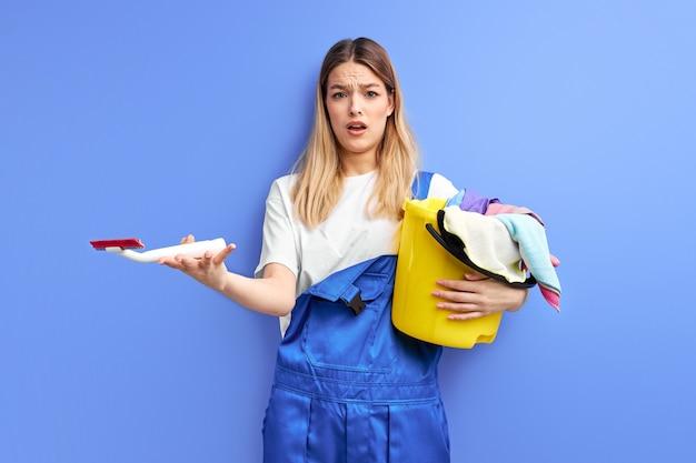 Mulher segurando balde com grupo de material de limpeza. jovem senhora de macacão em choque com a sujeira