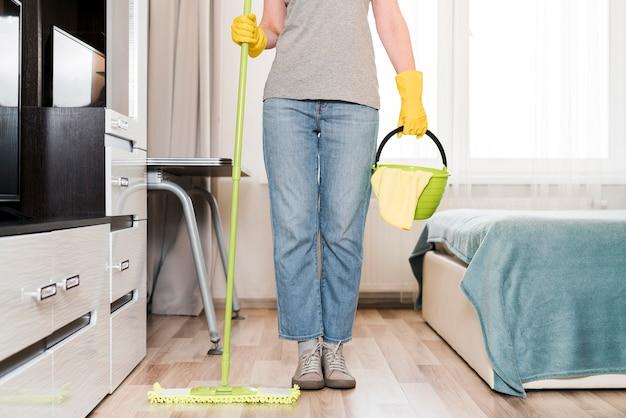 Mulher segurando balde e esfregão