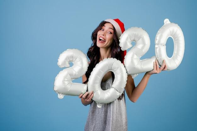 Mulher segurando balões de ano novo com vestido e chapéu de papai noel