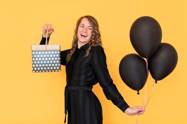 Mulher segurando balões e caixa de presente