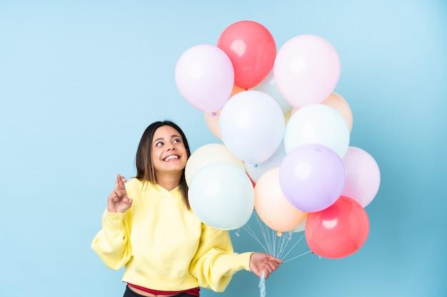Mulher segurando balões em uma festa ao longo da parede azul com dedos cruzando