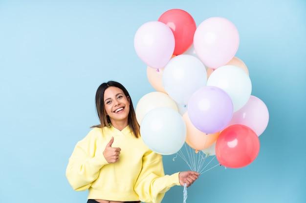 Mulher segurando balões em uma festa ao longo da parede azul, dando um polegar para cima gesto