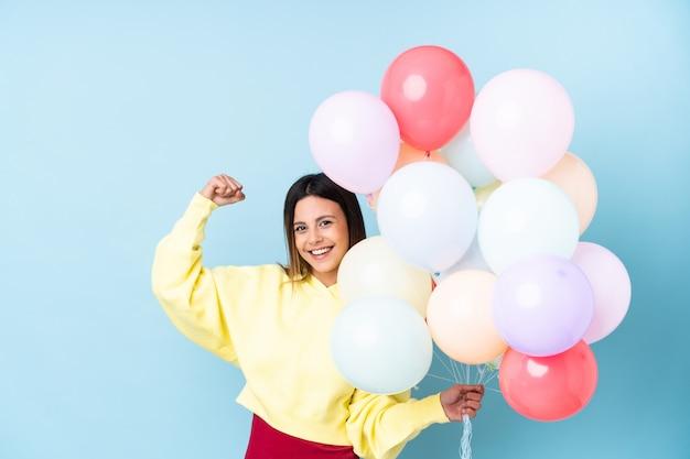 Mulher segurando balões em uma festa ao longo da parede azul, fazendo um gesto forte