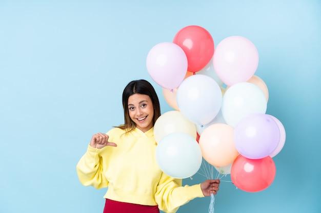 Mulher segurando balões em uma festa ao longo da parede azul, orgulhosa e satisfeita