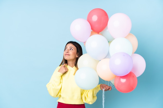 Mulher segurando balões em uma festa ao longo da parede azul, pensando em uma idéia