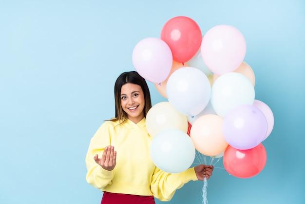 Mulher segurando balões em uma festa isolado parede azul convidando para vir