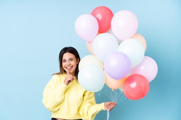 Mulher segurando balões em uma festa na parede azul, fazendo o gesto de silêncio