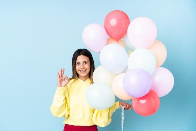 Mulher segurando balões em uma festa na parede azul, mostrando um sinal de ok com os dedos
