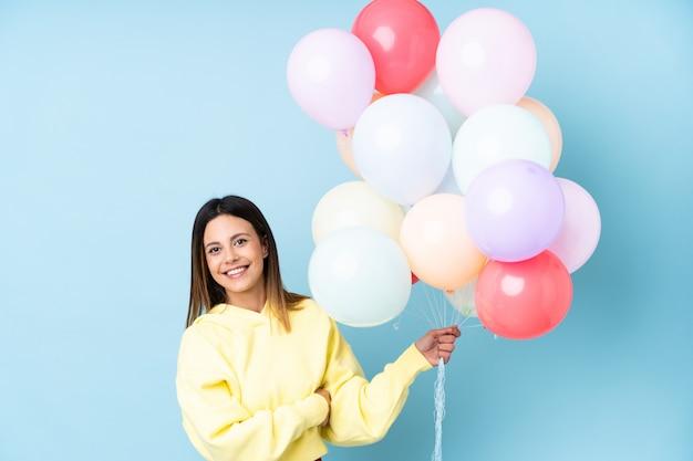 Mulher segurando balões em uma festa na parede azul, olhando para o lado
