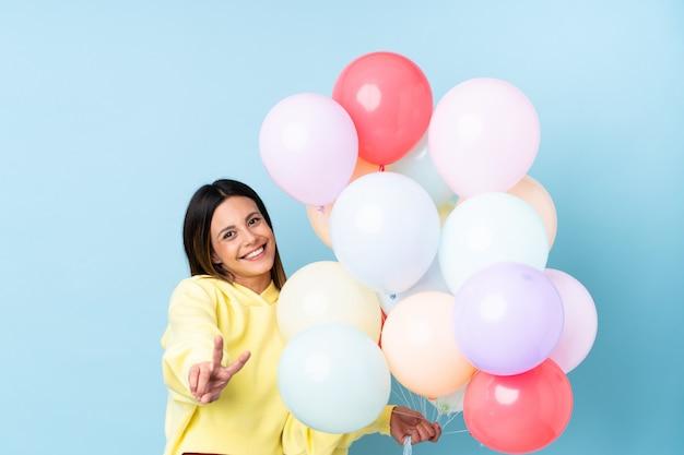 Mulher segurando balões em uma festa na parede azul sorrindo e mostrando sinal de vitória