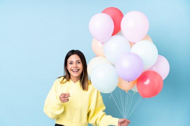 Mulher segurando balões em uma festa sobre parede azul aponta o dedo para você
