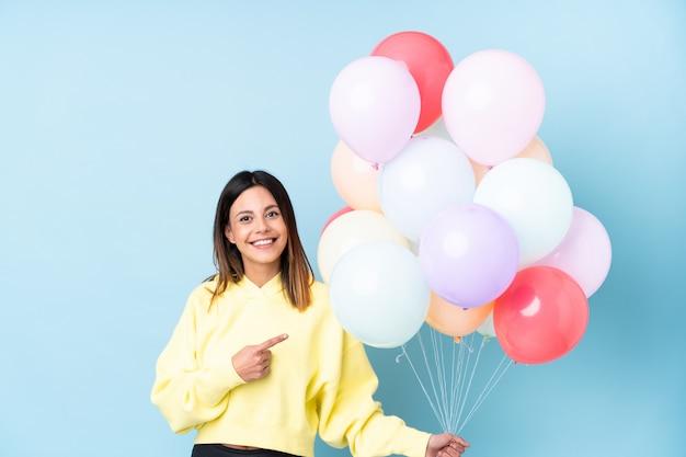 Mulher segurando balões em uma festa sobre parede azul, apontando o dedo para o lado