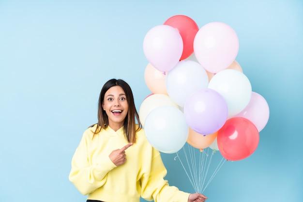 Mulher segurando balões em uma festa sobre parede azul isolada, apontando o dedo para o lado