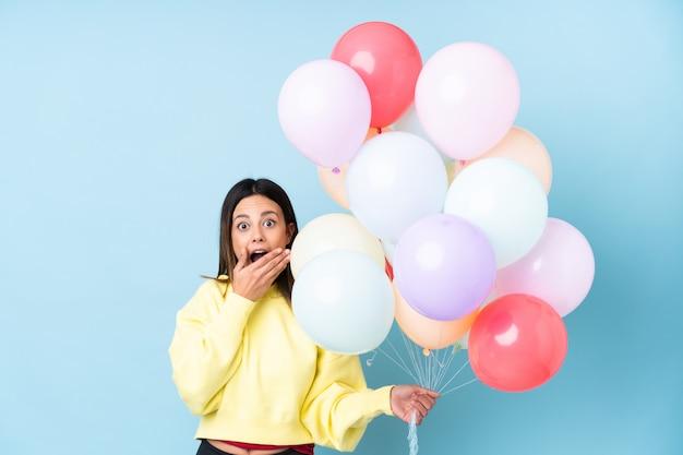 Mulher segurando balões em uma festa sobre parede azul isolada com expressão facial de surpresa