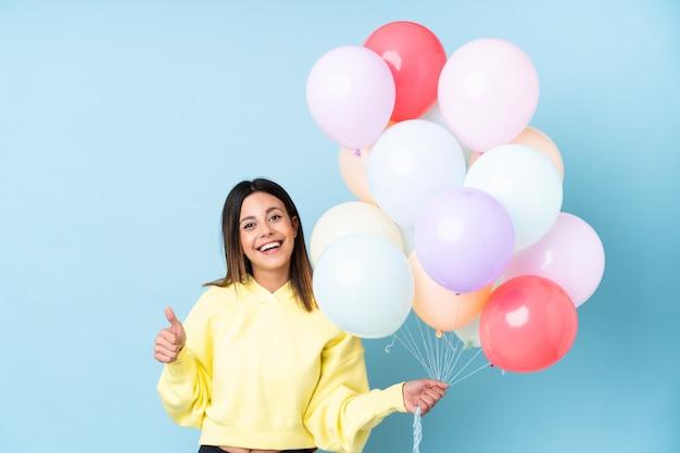 Mulher segurando balões em uma festa sobre parede azul isolada, dando um polegar para cima gesto