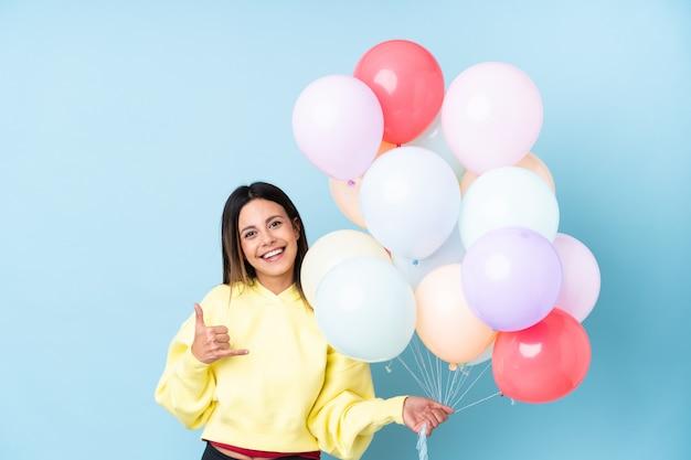 Mulher segurando balões em uma festa sobre parede azul isolada, fazendo gesto de telefone