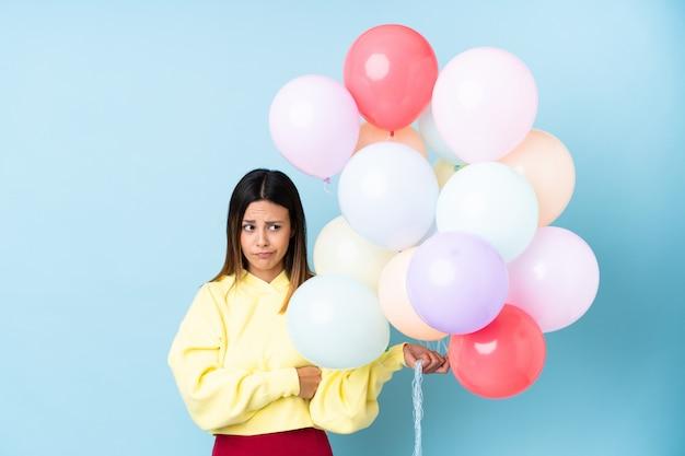 Mulher segurando balões em uma festa sobre parede azul isolada, pensando uma idéia