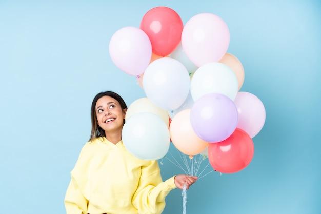 Mulher segurando balões em uma festa sobre parede azul isolada rindo e olhando para cima
