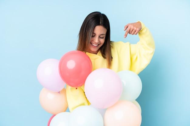 Mulher segurando balões em uma festa sobre parede azul isolada