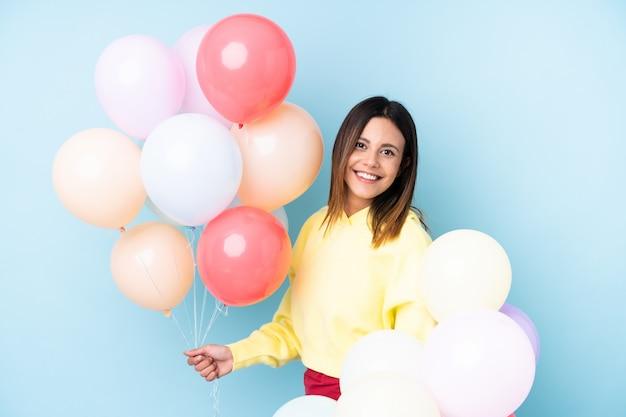 Mulher segurando balões em uma festa sobre parede azul