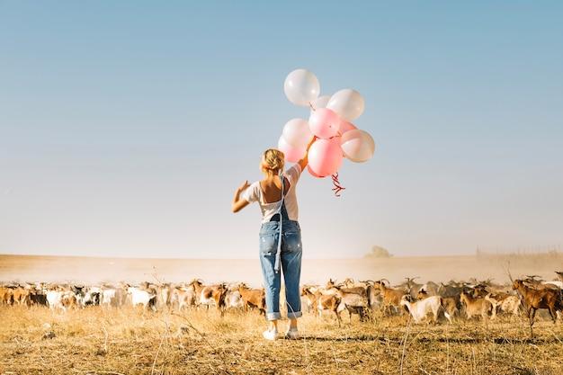 Mulher segurando balões perto de rebanho de cabra