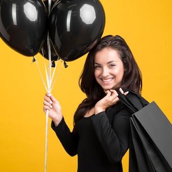Mulher segurando balões pretos com vista lateral