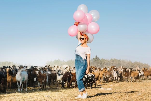 Mulher segurando balões sobre a cabeça perto de cabras