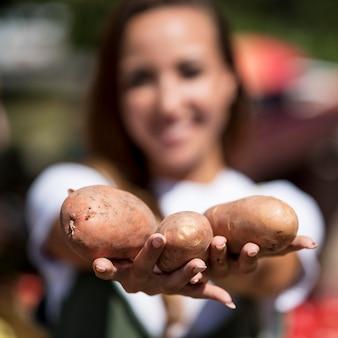 Mulher segurando batatas frescas