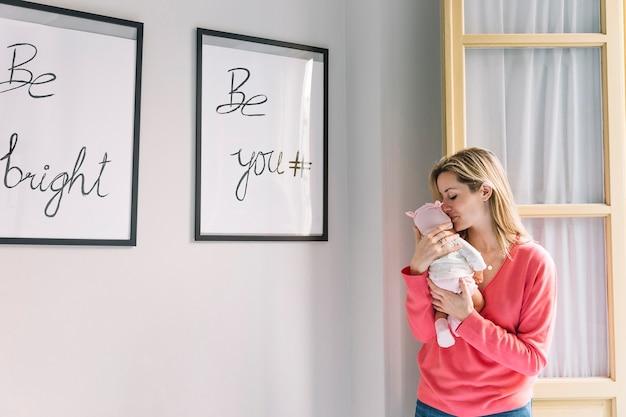 Mulher segurando bebê e quadros com citações