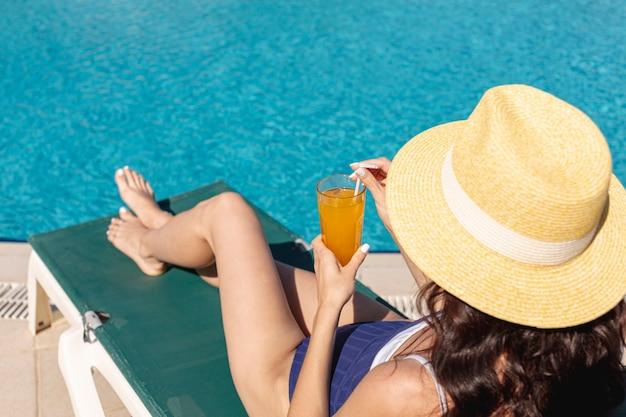 Mulher segurando bebida deitado na espreguiçadeira