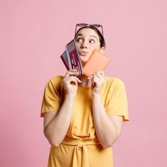 Mulher segurando bilhetes de avião e passaporte perto do rosto