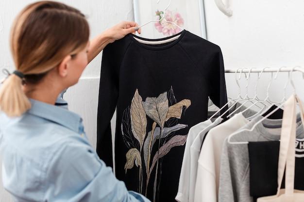 Mulher segurando blusa elegante