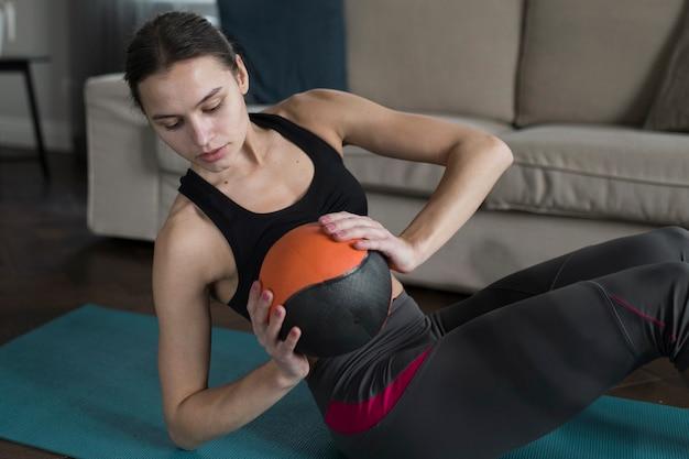 Mulher segurando bola durante o exercício
