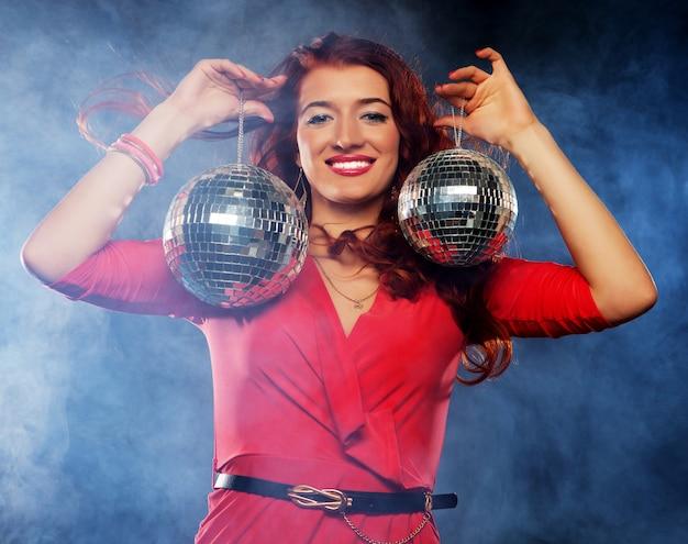 Mulher segurando bolas de discoteca na boate