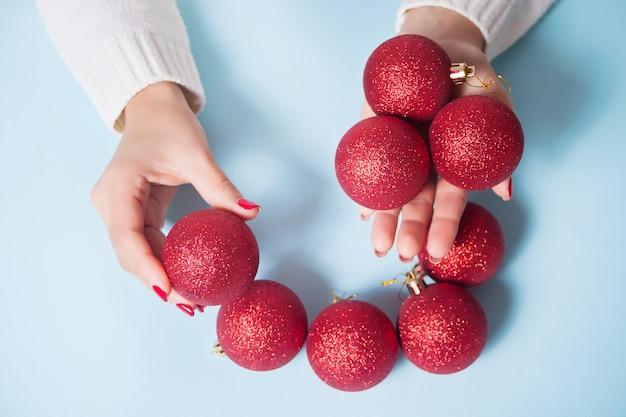 Mulher segurando bolas vermelhas de natal em uma mãos no azul