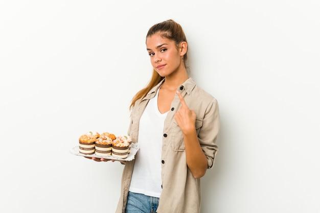 Mulher segurando bolos doces apontando com o dedo