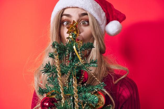 Mulher segurando brinquedos da árvore de natal, feriado isolado no fundo