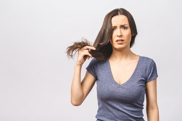Mulher segurando cabelo danificado com a mão