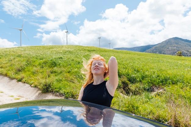 Mulher, segurando, cabelo, desfrutando, sol, saída, carro, janela