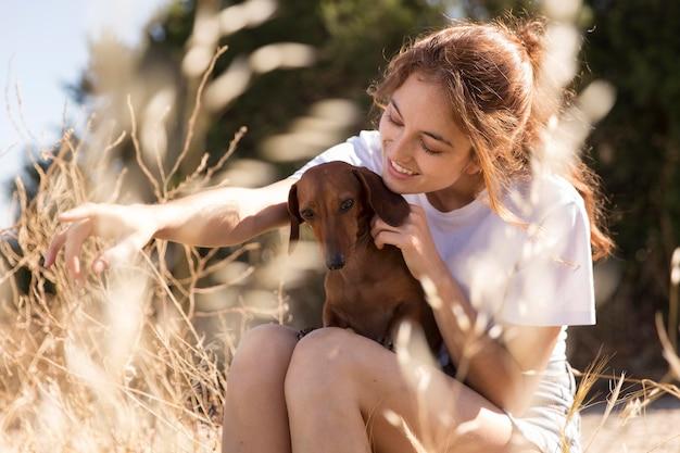 Mulher segurando cachorro fofo, tiro médio