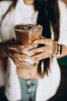 Mulher segurando café com leite gelado com gelo