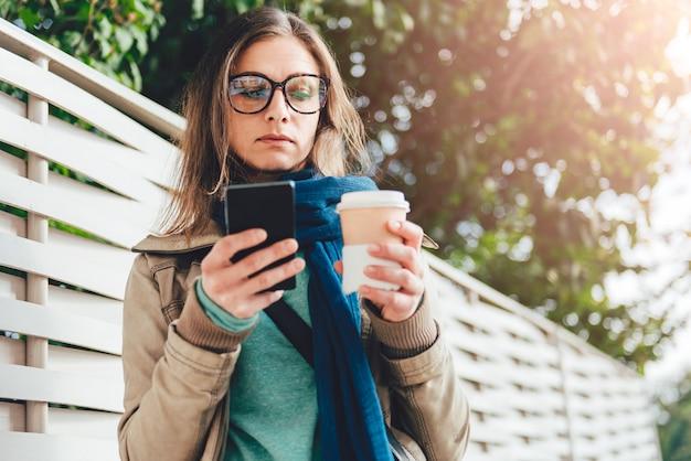 Mulher segurando café para viagem e usando telefone inteligente