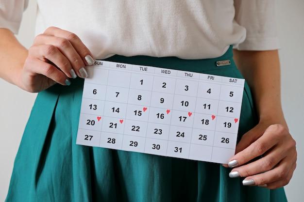 Mulher segurando calendário com datas marcadas de menstruação. cuidados de saúde de mulher e conceito de ginecologia.