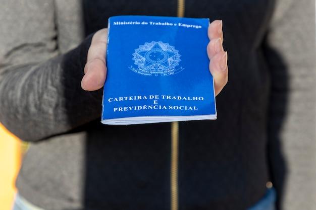 Mulher segurando cartão de trabalho brasileiro.