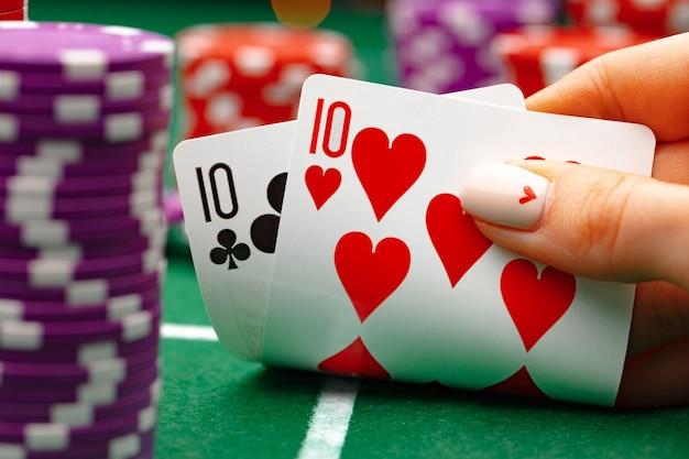 Mulher segurando cartas de jogar pôquer na mesa verde
