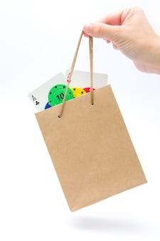 Mulher segurando cartas de pôquer e fichas de pôquer no saco isolado no fundo branco