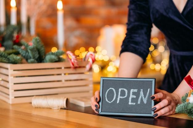 Mulher segurando cartaz aberto. quadro com palavra aberta sobre desfocar interior festivo.