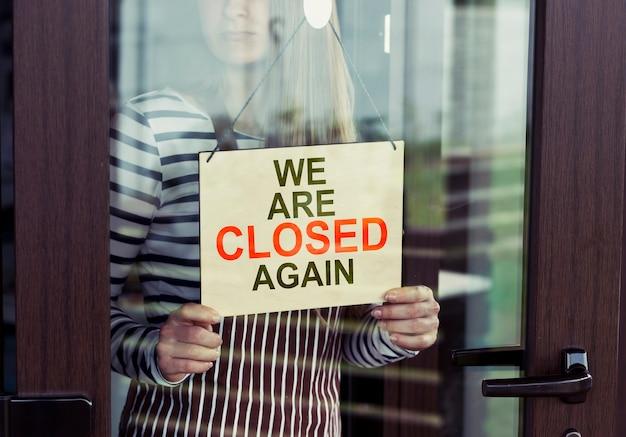 Mulher segurando cartaz de que estamos fechados