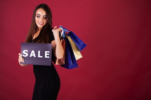 Mulher segurando cartaz de venda e sacolas de compras na parede vermelha