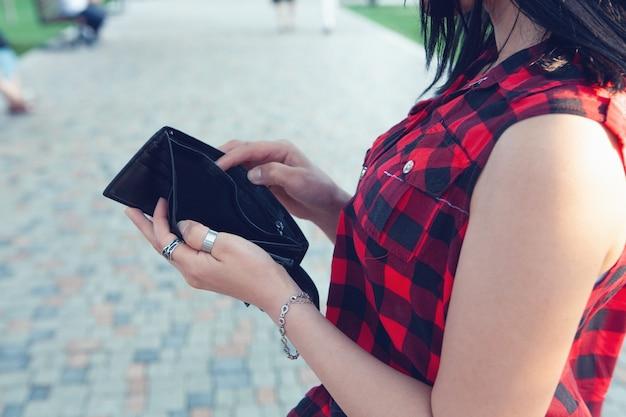 Mulher segurando carteira vazia na rua